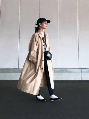 ボーダートップス、デニムスキニーパンツにベージュのステンカラーコートを着た女性