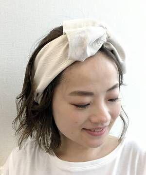 白のリボンヘアターバンを付けた女性