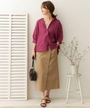 パープルシャツにベージュスカートを履いた女性