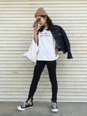 白のロゴTシャツにデニムジャケットを羽織り、黒のレギンスを合わせた女性