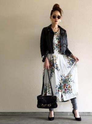 白の花柄ワンピースに黒のライダースを羽織り、グレーのレギンスを合わせた女性