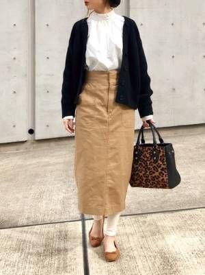 白のスタンドカラーブラウスに黒のカーディガンを羽織って、チノタイトスカートに白レギンスを合わせた女性