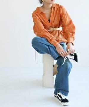 オレンジのストライプシャツにデニムパンツ、黒のスニーカーを合わせたコーデ