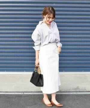 ストライプシャツに白のタイトスカート、キャメルのフラットシューズを合わせたコーデ