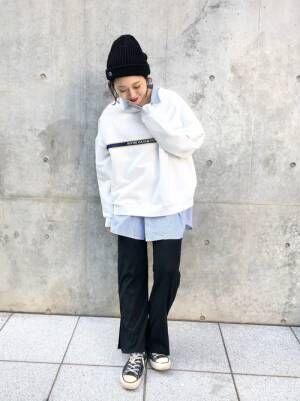 ストライプシャツにスウェットをレイヤードし、黒のパンツ、ニット帽を合わせたコーデ
