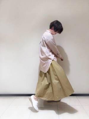 ストライプシャツにベージュのチノスカートを合わせたコーデ