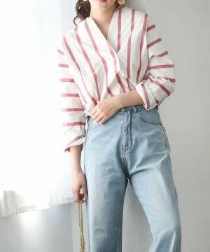 ストライプシャツにデニムパンツを履いた女性