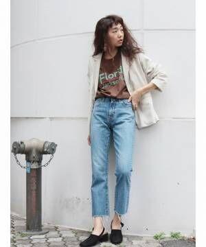 ブラウンTシャツに薄色デニムパンツを履いた女性