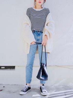 ボーダートップス、デニムパンツに白のカーディガンを着た女性