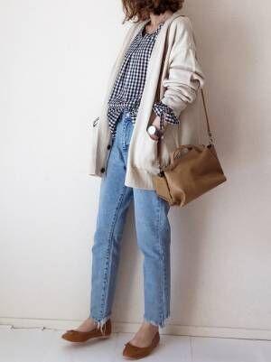 ギンガムチェックのブラウス、デニムパンツに白のカーディガンを着た女性