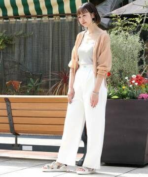グレーのトップス、白のパンツにベージュのカーディガンを着た女性