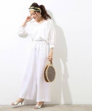 白のブラウスに白のワイドパンツを履いた女性