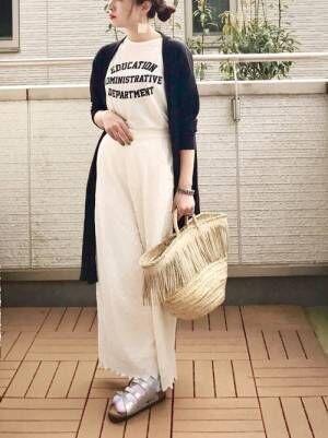 白のロゴT、白のワイドパンツに黒のカーディガンを着た女性