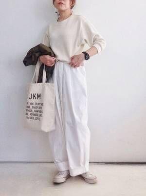 白のトップスに白のワイドパンツを履いた女性