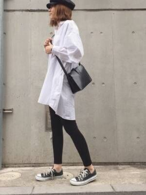 白にストライプが入ったビッグシャツに黒レギンスを合わせた女性
