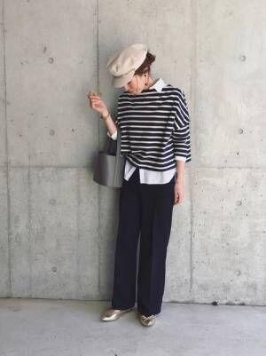 ボーダーのカットソーの中に白シャツをレイヤードして、黒のパンツを合わせた女性