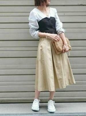 ストライプシャツにビスチェをレイヤードして、ベージュのスカートを合わせた女性