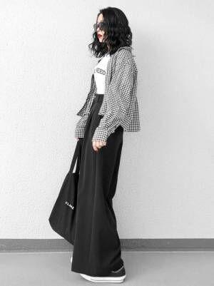 白のロゴTに黒のワイドパンツを合わせて、ギンガムチェックのシャツを羽織った女性