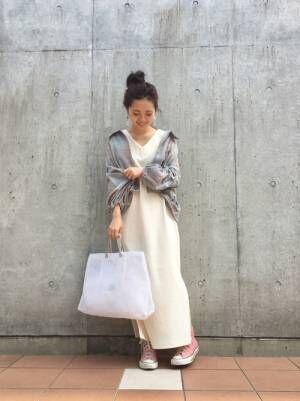 白のワンピースにガーゼのチェックシャツを羽織った女性