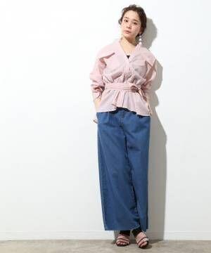 ピンクのノーカラーのベルト付きシャツにワイドデニムを合わせた女性