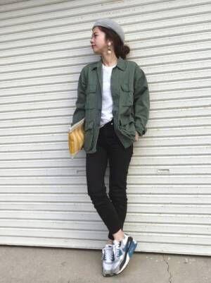 白のTシャツ、黒のスキニーパンツにカーキのミリタリージャケットを着た女性