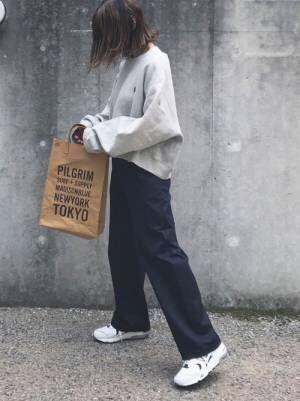 グレーのスウェットにネイビーのワイドパンツを履いた女性