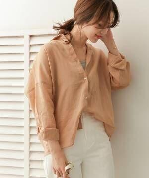 リネンシャツに白ボトムスを履いた女性