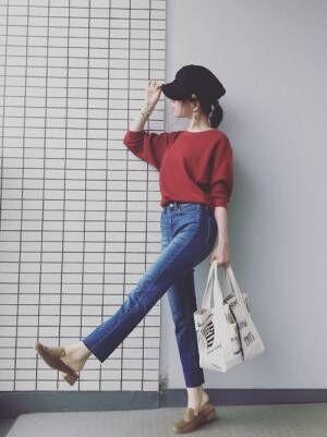 赤のワッフルクルーネックTにハイライズシガレットジーンズを合わせた女性