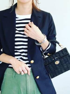 ボーダートップスに紺ブレを羽織って、ZARAのラフィア素材のミノディエールバッグを合わせた女性