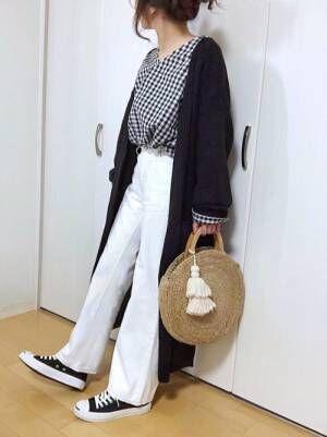 ギンガムチェックのブラウスに黒のロングカーデを羽織って、白のパンツを合わせた女性
