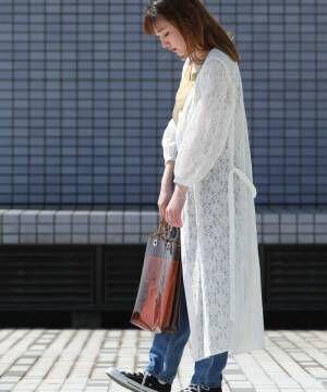 イエローのタンクトップにデニムを合わせて、白のレースの前開きワンピースを羽織った女性