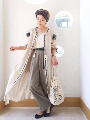 白のトップスにカーキのパンツを合わせて、ベージュの刺繍ワンピースを羽織った女性