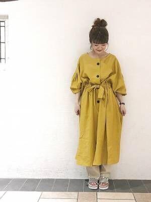 黄色の前開きワンピースにベージュのリブニットパンツを合わせた女性