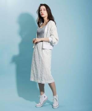 グレーのトップス、白のスカートに白のブルゾンを着た女性