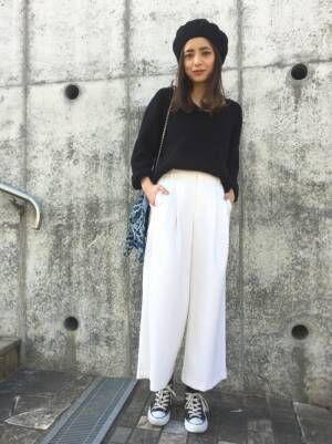 黒のトップスに白のワイドパンツを履いた女性