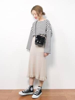 ボーダートップスに白のニットスカートを履いた女性