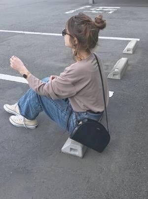 グレージュのトップスにワイドデニムを履いた女性