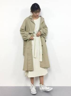 白のワンピースにベージュのトレンチコートを着た女性
