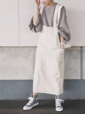 グレーのスウェットに白のジャンパースカートを着た女性