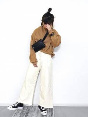 キャメルのスウェットトップスに白のスウェットパンツを履いた女性