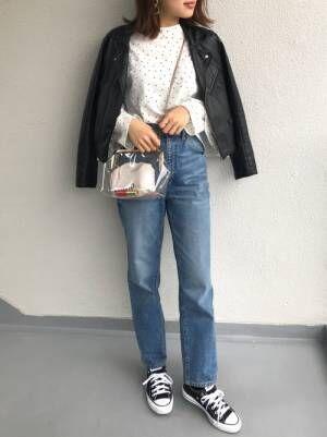 白のドットブラウスにデニムパンツ、ライダースジャケットを羽織ったコーデ