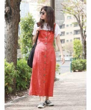白のTシャツに赤のジャンパースカートを着た女性