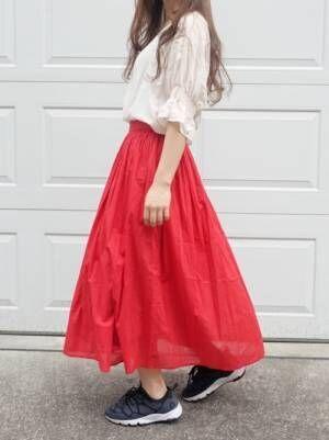 白のブラウスに赤のギャザースカートを履いた女性