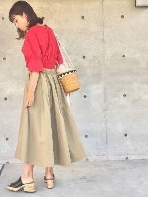 赤のトップスにベージュのギャザースカートを履いた女性