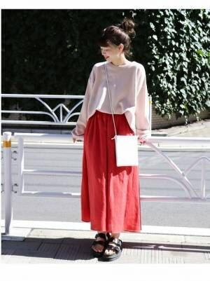 ピンクのスウェットに赤のスカートを履いた女性