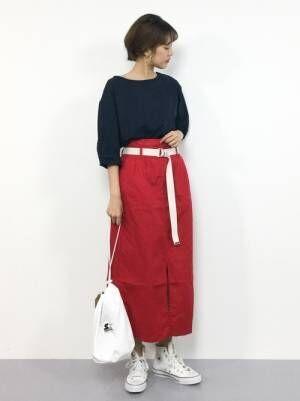 黒のトップスに赤のタイトスカートを履いた女性