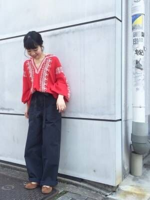 赤の刺繍ブラウスにネイビーのワイドパンツを履いた女性