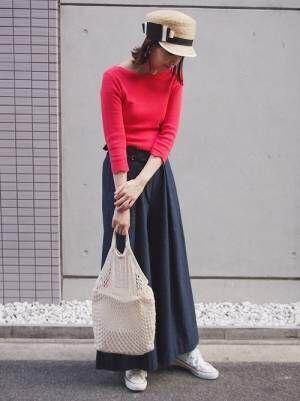 赤のトップスにネイビーのワイドパンツを履いた女性