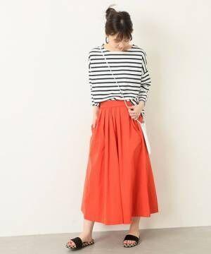 ボーダートップスに赤のギャザースカートを履いた女性