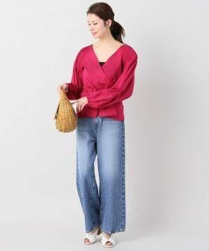 赤のブラウスにワイドデニムを履いた女性